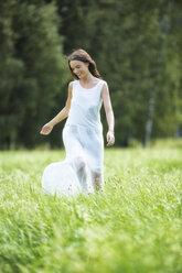 Happy woman wearing white summer dress walking on a meadow - MAEF12019