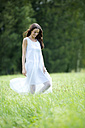 Happy woman wearing white summer dress walking on a meadow - MAEF12022