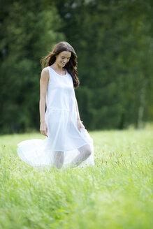 Happy woman wearing white summer dress walking on a meadow - MAEF12022
