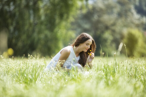 Woman crouching on a meadow smelling flowers - MAEF12025