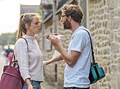 France, Bretagne, young couple eating Crepes - LAF01728