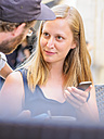 Portrait of blond young woman with smartphone face to face with her boyfriend - LAF01734