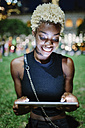 Smiling young woman sitting on meadow of a park at night using tablet - GIOF01459