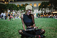 Young woman sitting on meadow of a park at night using tablet - GIOF01462