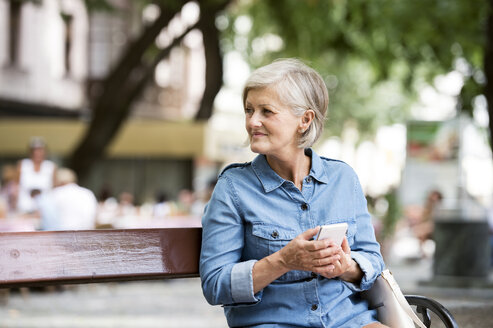 Senior woman with smartphone sitting on bench in the city - HAPF00908