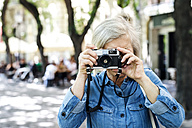 Senior woman taking picture with camera - HAPF00941