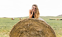Portrait of smiling blond teenage girl lying on straw bale - MGOF02436
