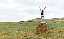 Back view of teenage girl standing on straw bale on a meadow raising arms - MGOF02442