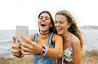 Two best friends taking selfie with smartphone at the coast - MGOF02448