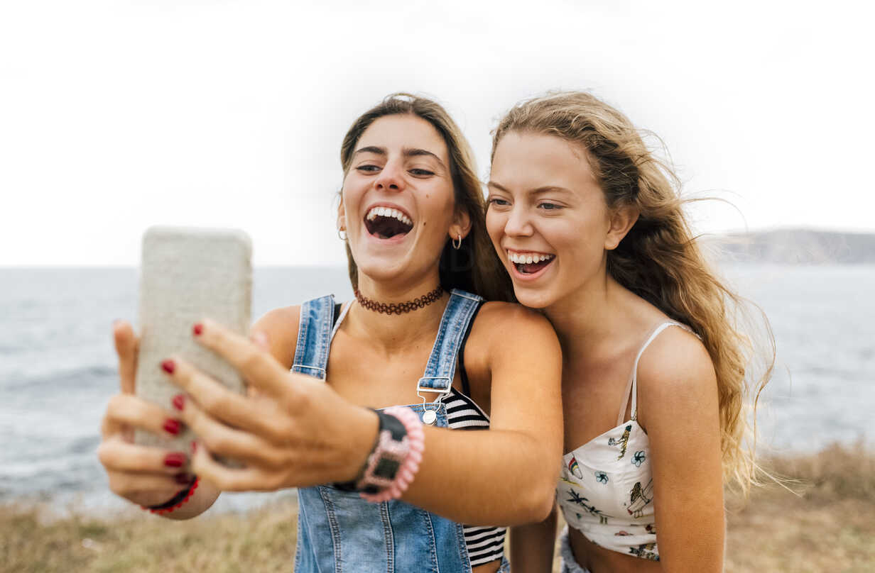 Two best friends taking selfie with smartphone at the coast - MGOF02448 - Marco Govel/Westend61