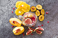Glass of infused water with orange slices, fig, pomegranate seed, nectarine and plums - SARF02906