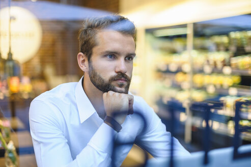 Businessman in a cafe looking through window - DIGF01224