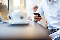 Close-up of businessman with cell phone and laptop in a cafe - DIGF01230