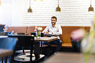 Smiling businessman sitting in a cafe with cup of coffee - DIGF01239