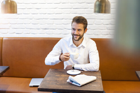 Smiling businessman sitting in a cafe with cup of coffee - DIGF01242