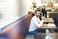 Businessman sitting in a cafe with cup of coffee - DIGF01248