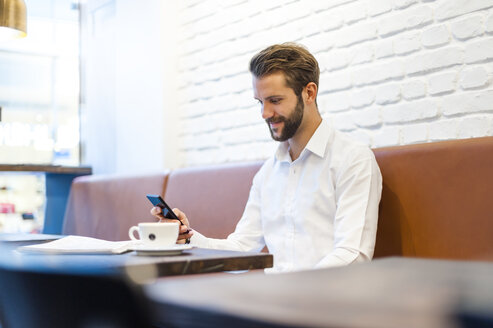 Smiling businessman looking at cell phone in a cafe - DIGF01251