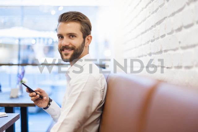 Smiling businessman with cell phone in a cafe - DIGF01254