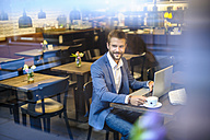 Smiling businessman with laptop in a cafe - DIGF01257