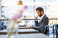 Businessman drinking coffee and using laptop in a cafe - DIGF01266