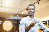 Smiling businessman holding cup of coffee behind windowpane  in a cafe - DIGF01269