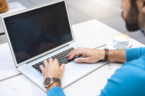 Close-up of businessman analyzing data on laptop display - DIGF01293