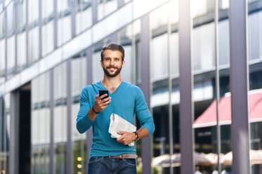 Smiling young man holding cell phone and newspaper in the city - DIGF01305