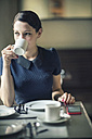 Young woman drinking coffee in a cafe - TAMF00661