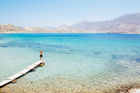 Greece, Cyclades islands, Amorgos, Aegean Sea, man standing on the edge of a wooden dock - GEMF01018
