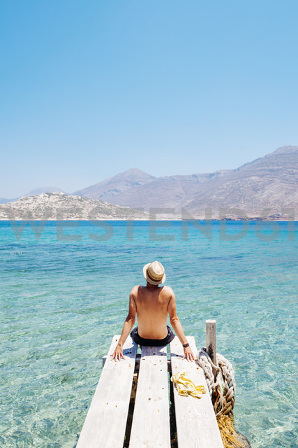 Greece, Cyclades islands, Amorgos, man sitting on the edge of a wooden pier, Nikouria island - GEMF01021