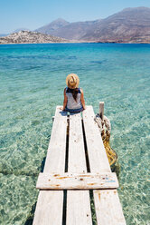 Greece, Cyclades islands, Amorgos, woman sitting on the edge of a wooden pier, Nikouria island - GEMF01024