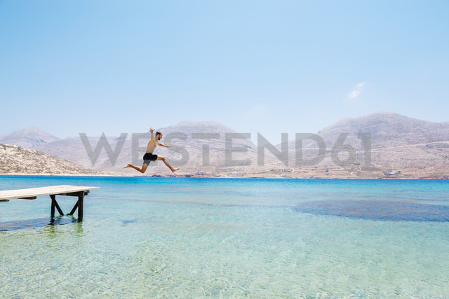 Greece, Cyclades islands, Amorgos, Aegean Sea, naked man jumping from a wooden jetty - GEMF01030