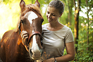 Smiling young woman with horse - MAEF12037