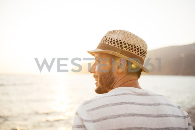 Greece, Cylcades Islands, Amorgos, man enjoying the sunset next to the sea - GEMF01031