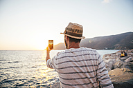 Greece, Cylcades Islands, Amorgos, man taking pictures of the sunset with a smartphone next to the sea - GEMF01034