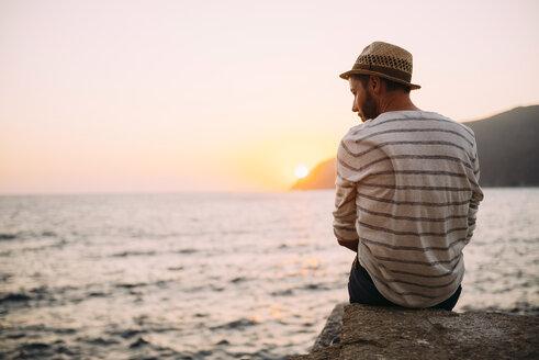 Greece, Cylcades Islands, Amorgos, man sitting at the sea at sunset - GEMF01040