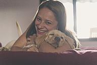 Portrait of happy young woman cuddling her Labrador Retriever puppy - SKCF00199