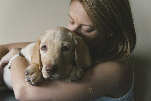 Young woman cuddling her Labrador Retriever puppy - SKCF00205