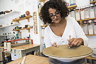 Woman decorating a plate in a ceramics workshop - ABZF01247