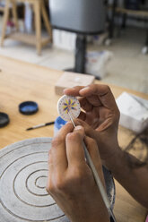 Woman painting a ceramic pendant with a brush - ABZF01253