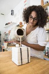 Woman pouring liquid porcelain into a mold - ABZF01259