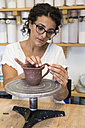 Woman placing the handle of a cup of clay in a ceramic workshop - ABZF01262