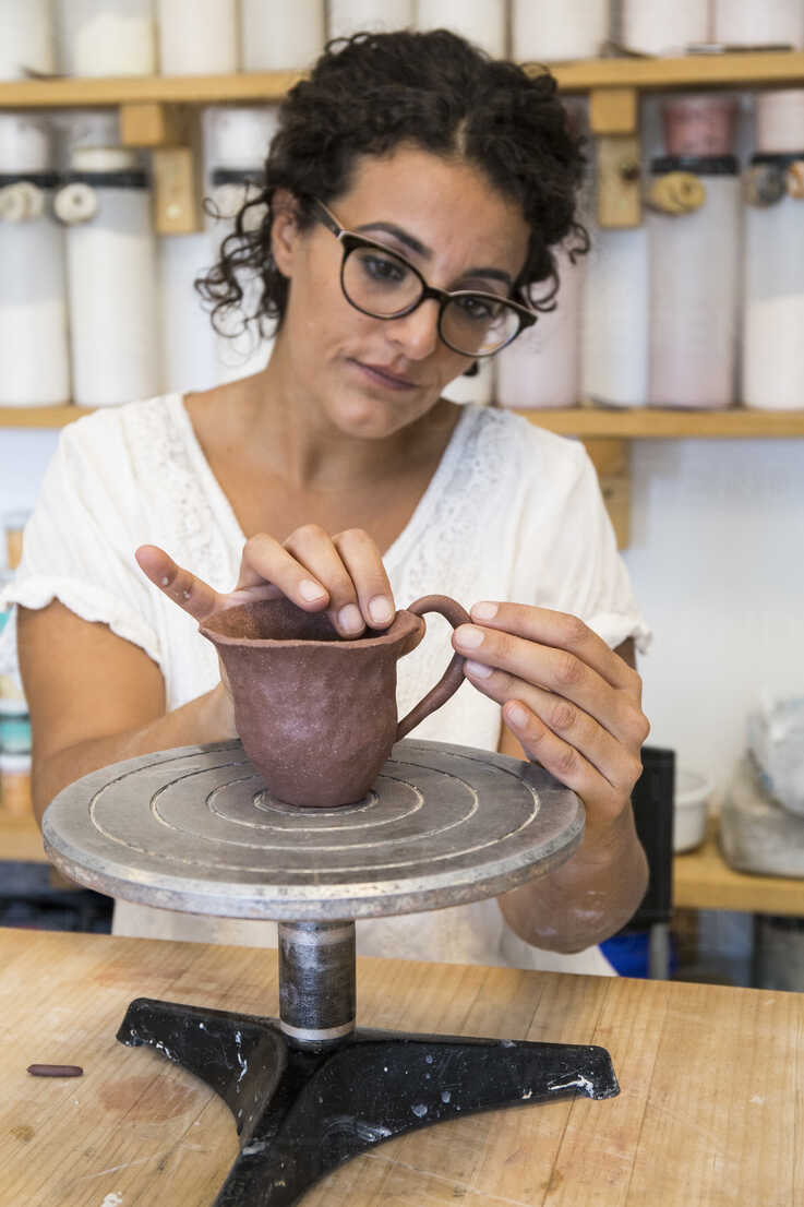 Woman placing the handle of a cup of clay in a ceramic workshop - ABZF01262 - Andrés Benitez/Westend61