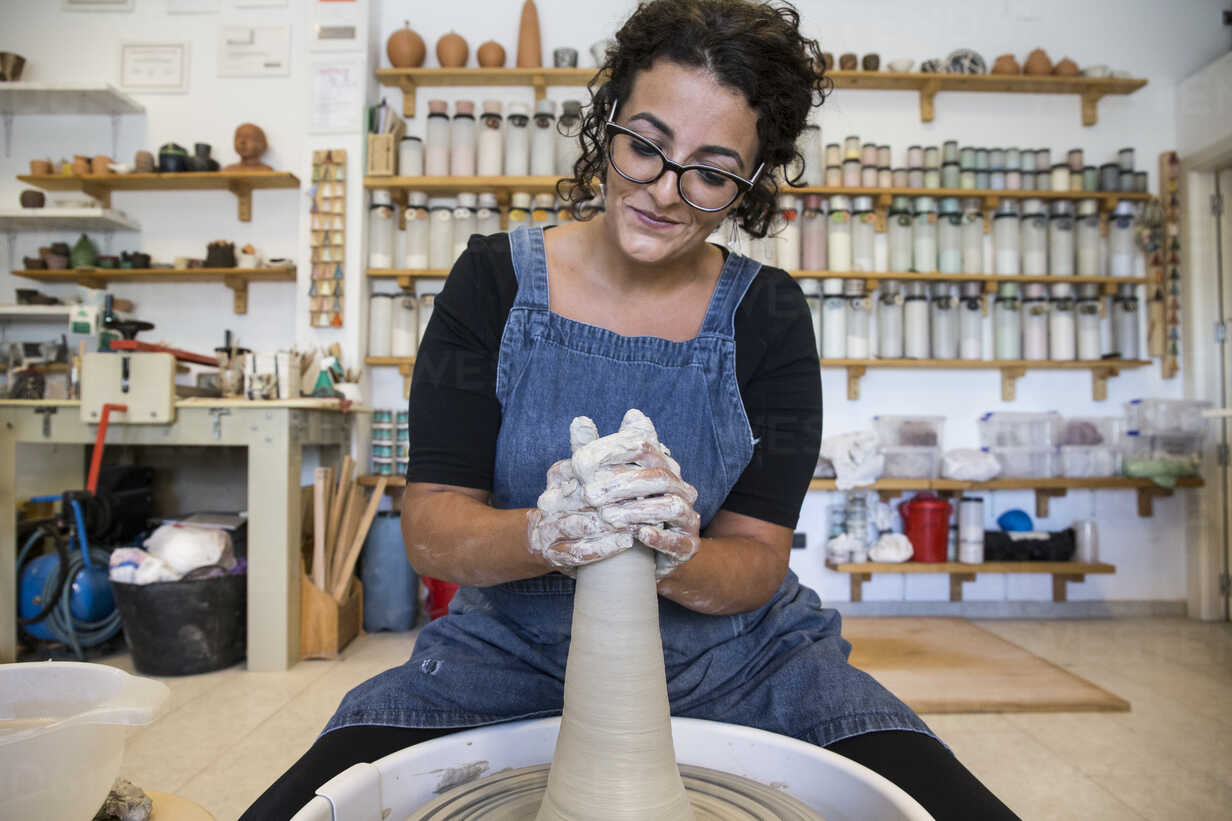 Woman working with a potter's wheel in a ceramics workshop - ABZF01268 - Andrés Benitez/Westend61