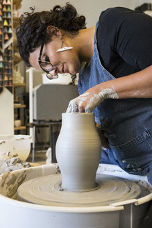Woman working with a pottery wheel in her workshop - ABZF01274