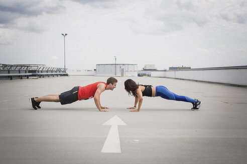 Man and woman doing push ups outdoor - ASCF00657