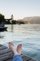 Austria, Sankt Wolfgang, woman's feet on jetty at lake - JUNF00629
