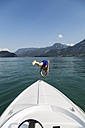 Austria, Sankt Wolfgang, man jumping from boat into lake - JUNF00635