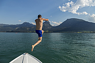 Austria, Sankt Wolfgang, man jumping from boat into lake - JUNF00638