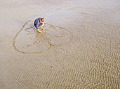 Woman at the beach drawing heart into the wet sand - LAF01748